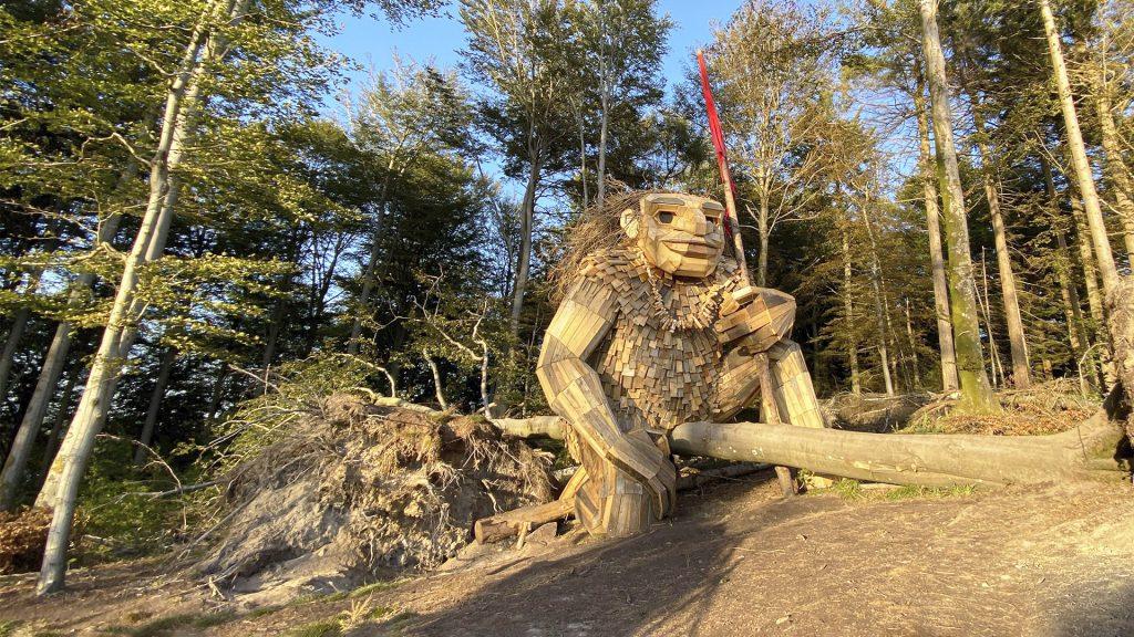 Træskulptur udformet som en kæmpetrold der knæler i skoven