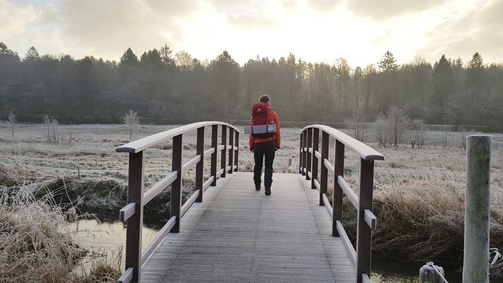 Vandre på træbro i vinterlandskab med rimfrost