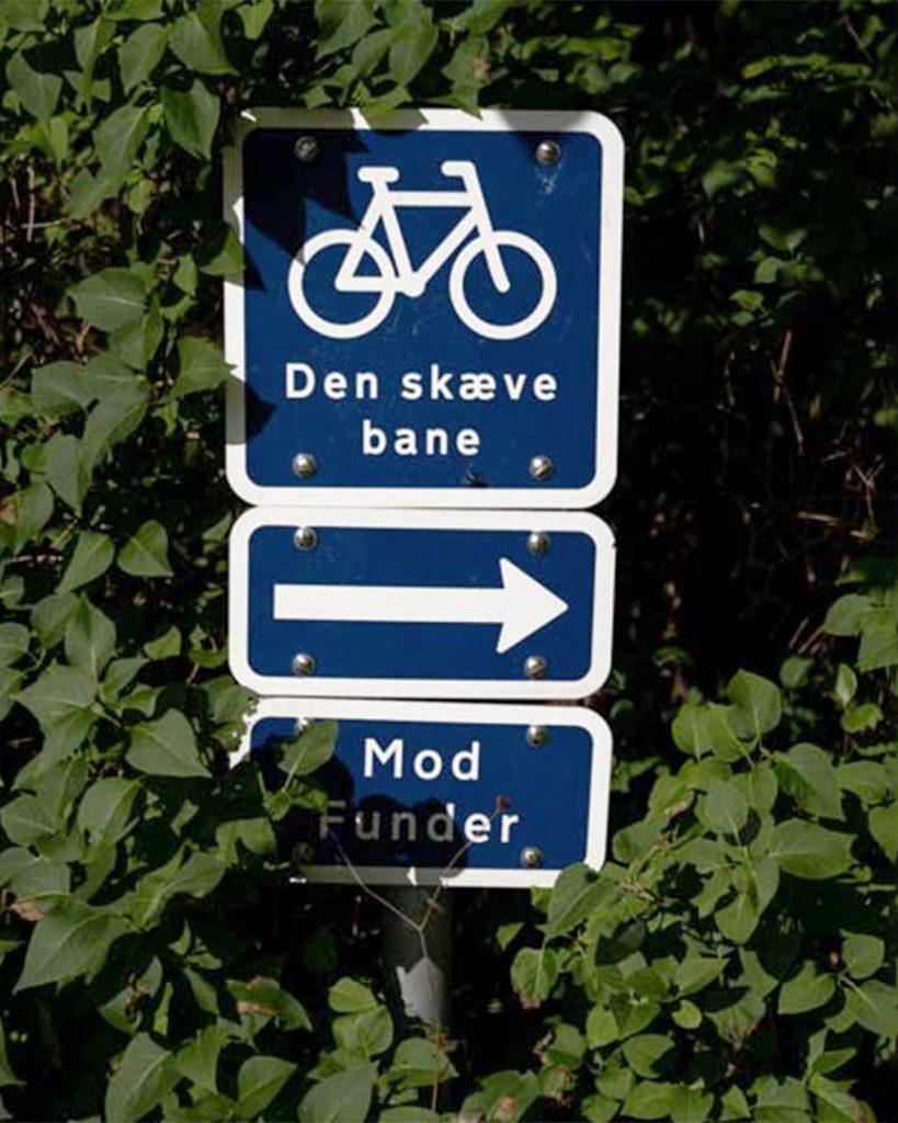 Cykelskilt i grøn bevoksning der viser vej mod Funder