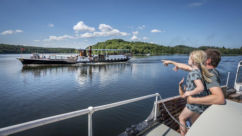 barn på båd der peger på hjuldamperen Hjejlen
