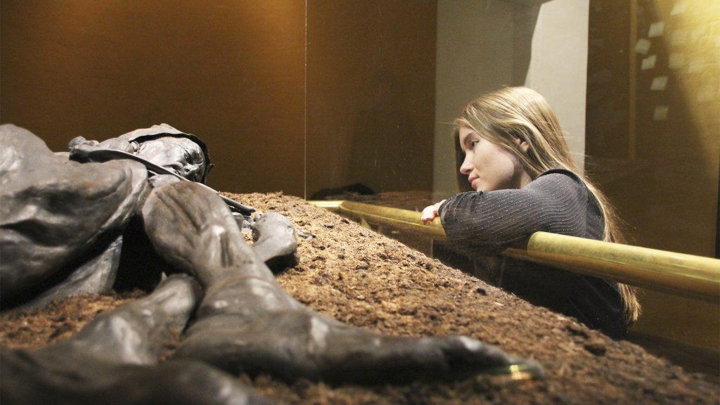 Ung pige der står ved montre og kigger på Tollundmanden
