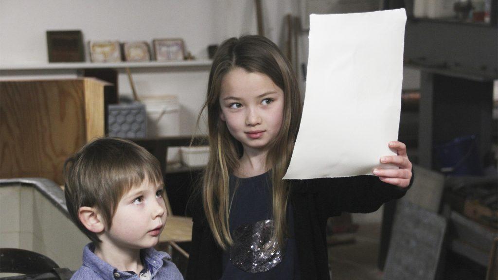 To børn der står og kigger på et stykke papir