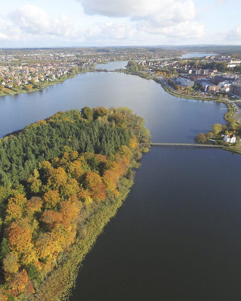 Luftfoto af Odden der stikker ud i Silkeborg Langsø med Silkeborg by i baggrunden