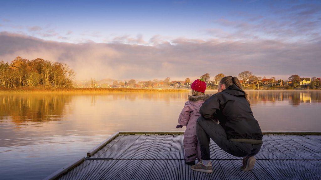 Mor med datter på bådebro med Odden i dis i baggrunden