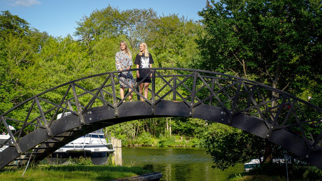To piger der står på en bro over remstrup å