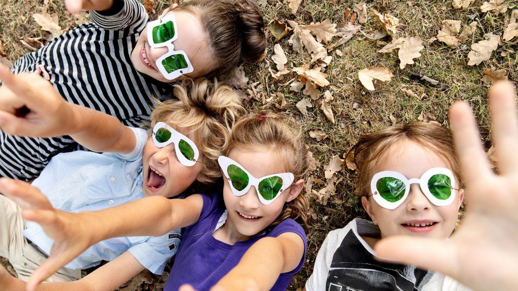 Børn med solbriller der ligger i græsset